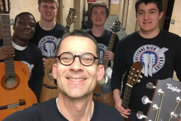 guitar teacher taking a selfie with guitar students in background