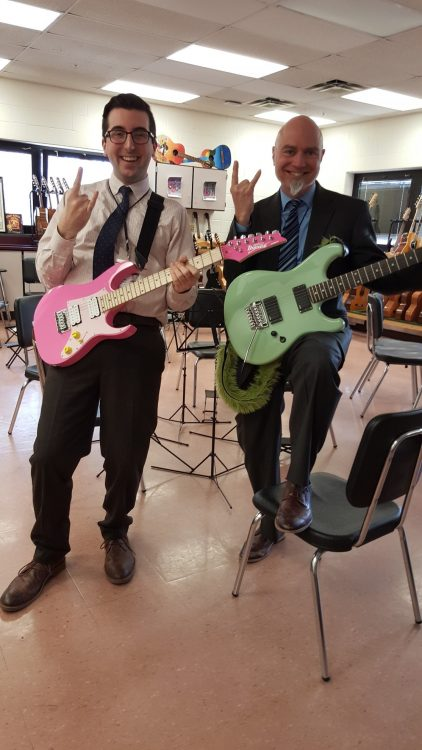 student teacher and cooperating teacher with pink and green electric guitars and rock and roll hand gestures