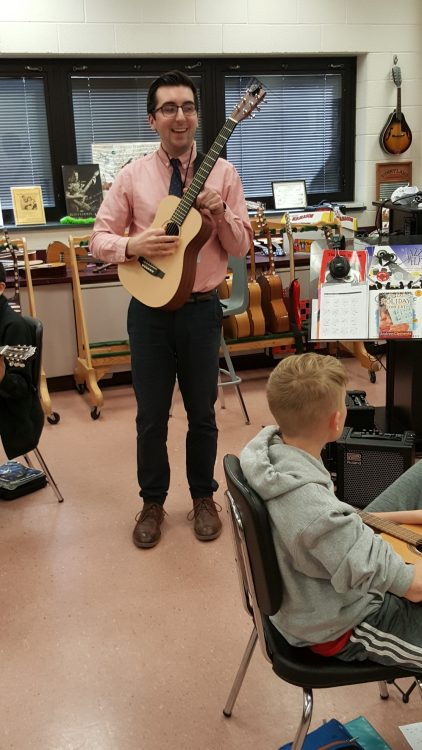 student teacher with glasses wearing salmon button down in a guitar classroom