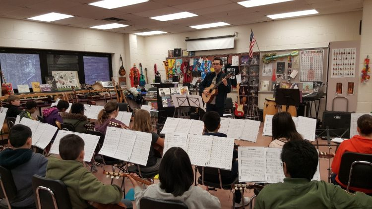 students sitting in guitar classroom with music stands and sheet music