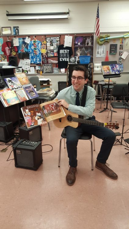 male student teacher reading picture book in guitar class