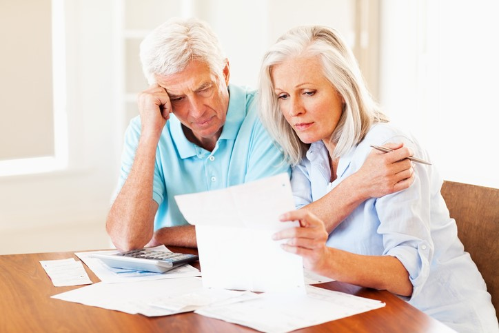 Concerned senior couple calculating home finances at a table