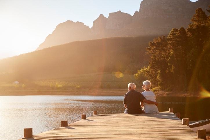 retired couple sitting on dock at lake