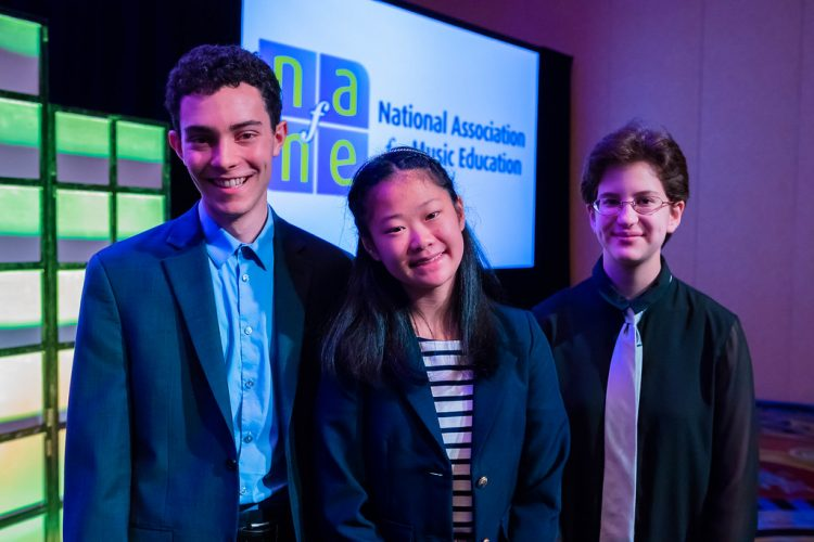 three smiling students on stage with National Association for Music Education logo on screen in background