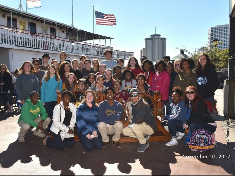 group class photo outside with New Orleans steamboat in background