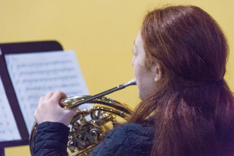 girl rehearsing on horn in front of music stand playing musical phrases