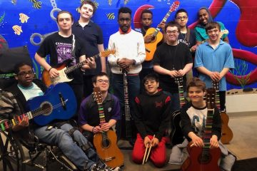 3 Strings UnLoCkeD guitar ensemble group photo with members posing with their string instruments