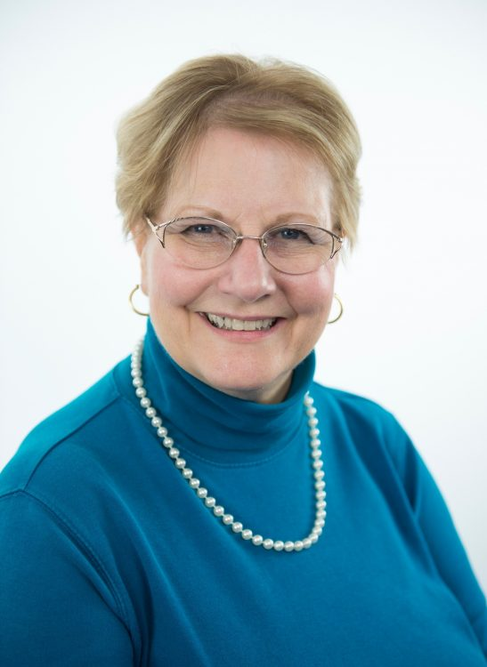 Headshot of Janice Smith wearing blue blouse and pearls