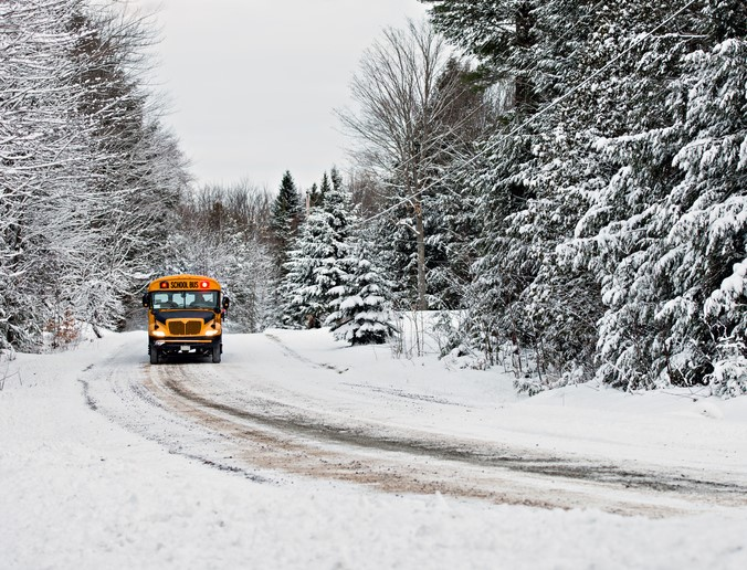 School Bus Driving Down a Snow Covered Road