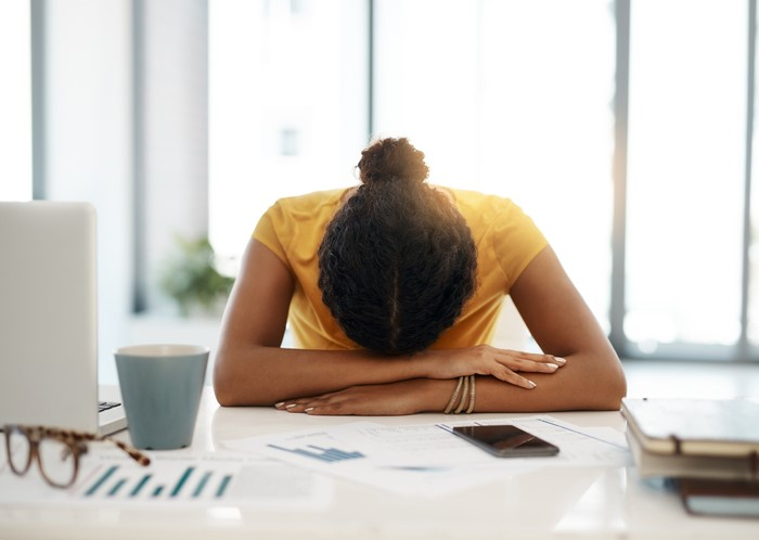 young woman with her head down on her office desk