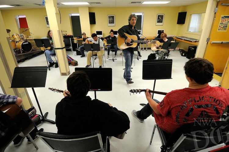 guitar teacher and seated guitar students in classroom in Arkansas the natural state
