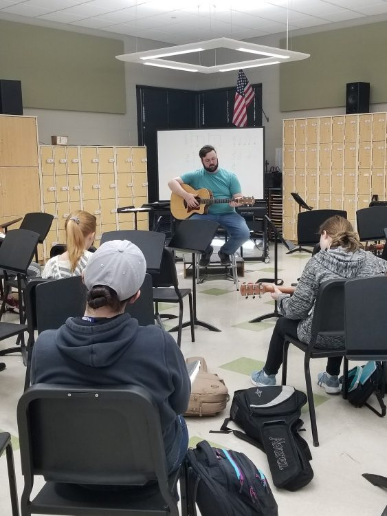 guitar teacher Sam Johnson in class with students