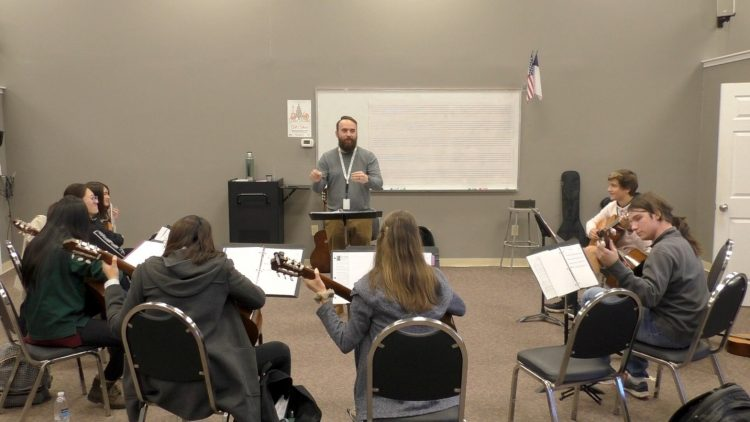students sitting in guitar class in the Palmetto state with teacher Chris Essig