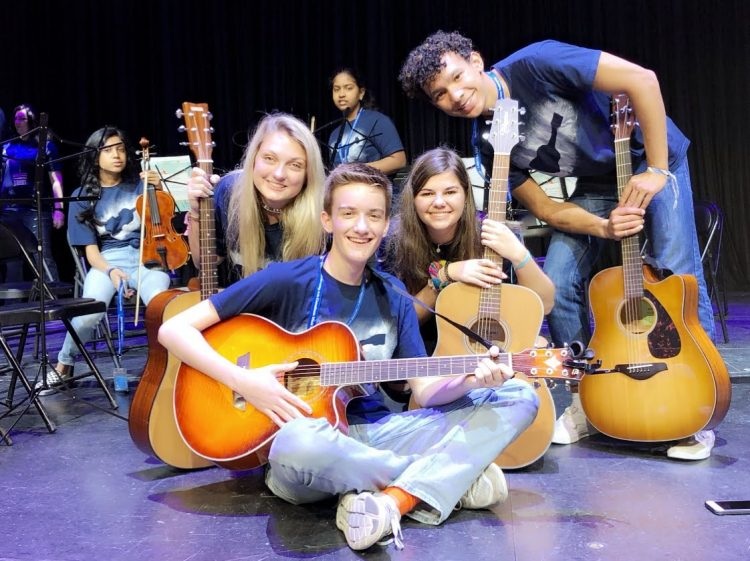 group photo of guitar students sitting on stage