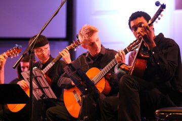 three male students playing guitar