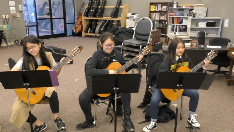 three female students playing guitar in class