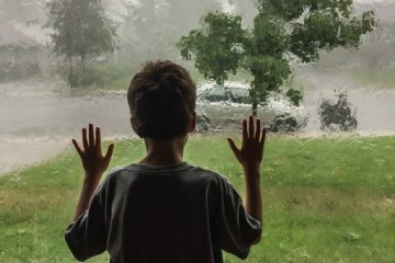 Litlle boy seen from behind and looking at the rain storm through living room window