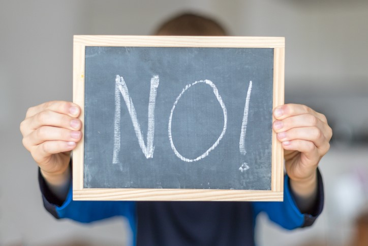person holds blackboard with NO letters