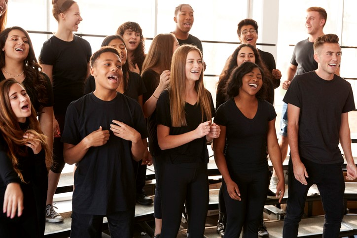 Male And Female Students showing creative expression wearing black shirts and pants Singing In Choir