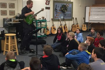 Nate Jackson teaching guitar class with students sitting on floor