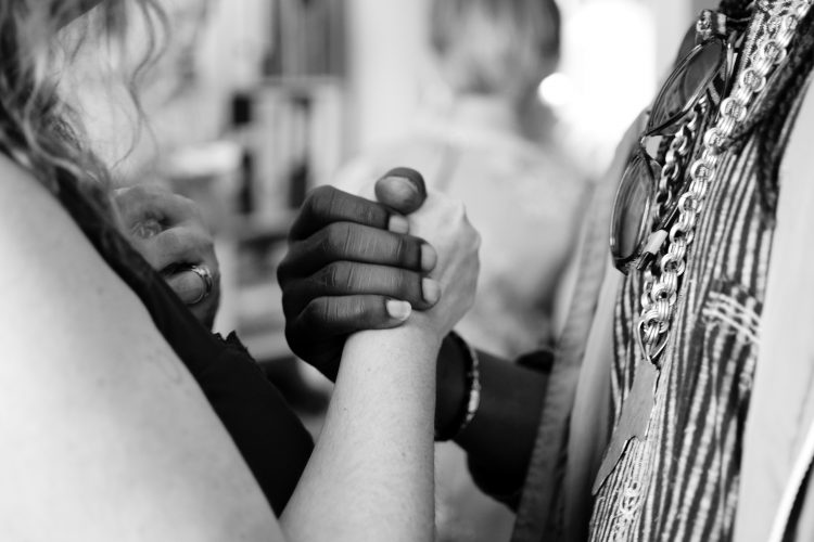 grayscale photo of white woman and black man holding hands in unity