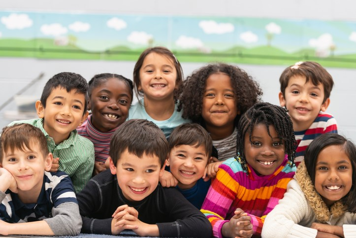 A group of diverse kids smile in this portrait.