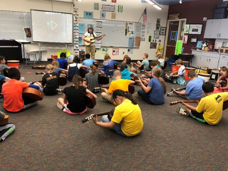 guitar students sitting on floor with instruments