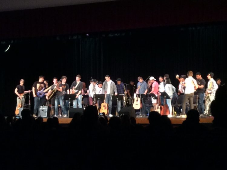 guitar students standing on stage