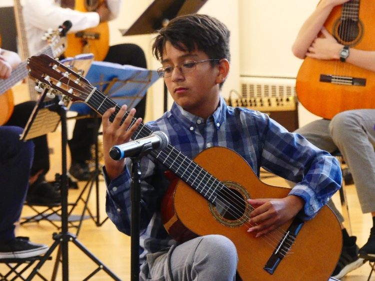 young boy with glasses playing guitar