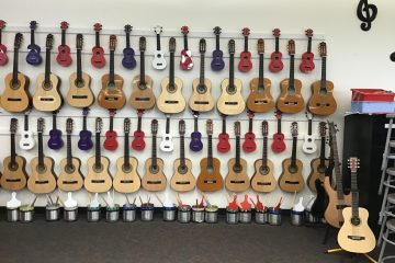 guitars and ukuleles stored hanging on classroom wall