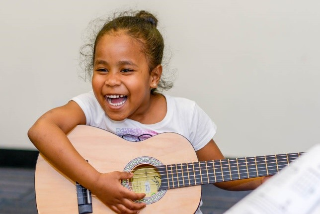 smiling girl with guitar