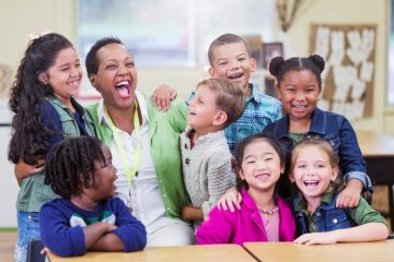 An African-American teacher in an elementary school classroom with seven multi-ethnic boys and girls, 6 and 7 years old. They are having fun, excited to be in school, laughing and smiling.