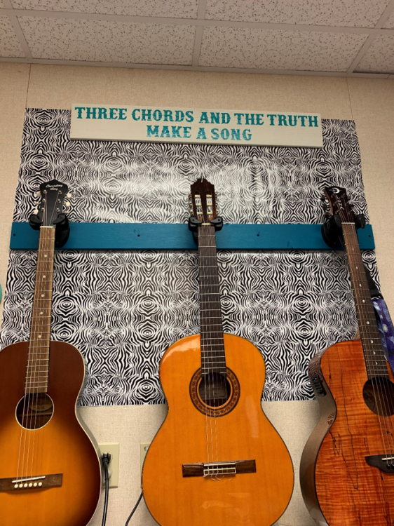 three guitars on display with bulletin board reading three chords and the truth make a song