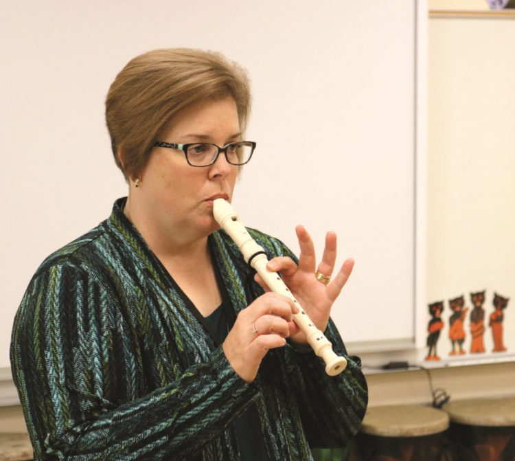 Karen Dickinson playing the recorder in music classroom