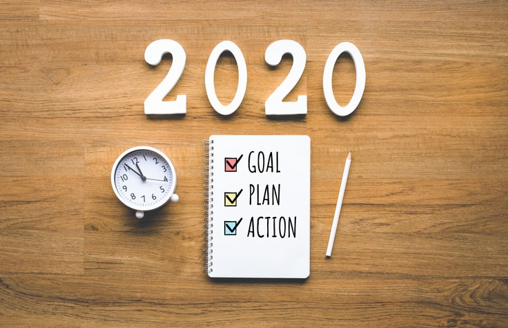 2020 new year goal plan action text on notepad on wood background