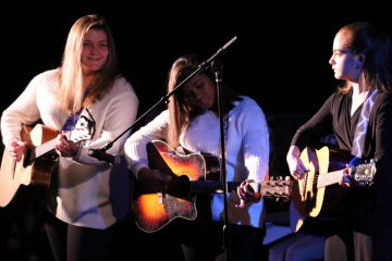 three female students with guitars
