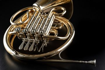 French horn on a wooden table. Beautiful polished musical instrument. Dark background.