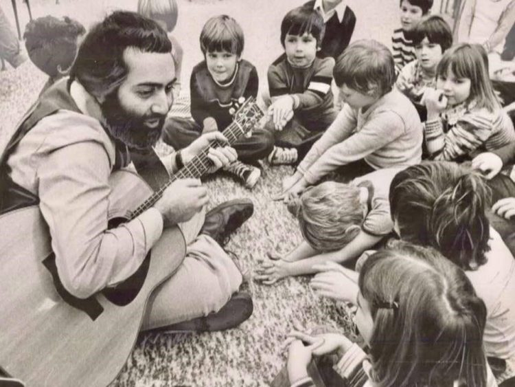 sepia toned photo of Raffi singing with children