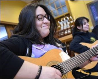 smiling female guitar student