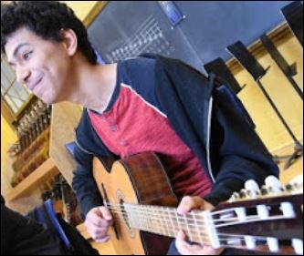 smiling male guitar student
