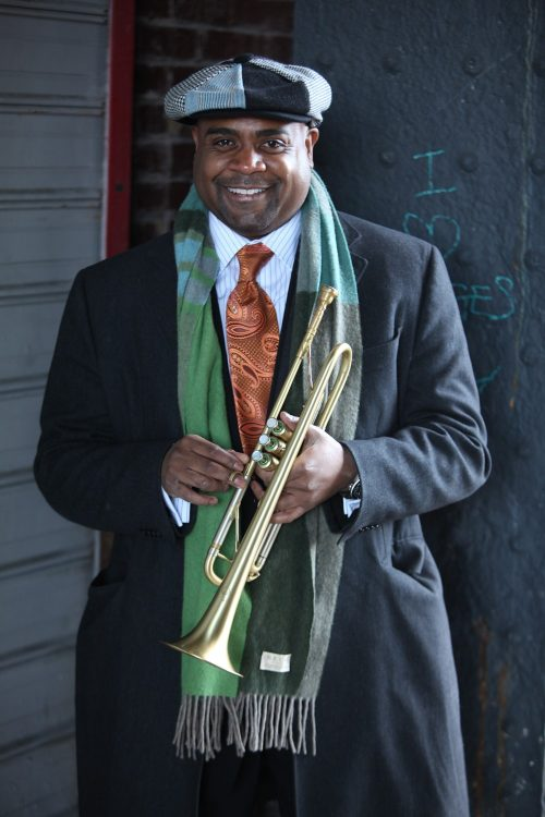 Terell Stafford wearing hat and scarf smiling and holding trumpet