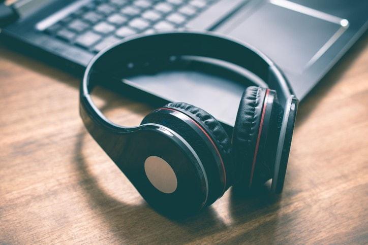Black Wireless Headphones Lying on the Corner of a Laptop Keyboard