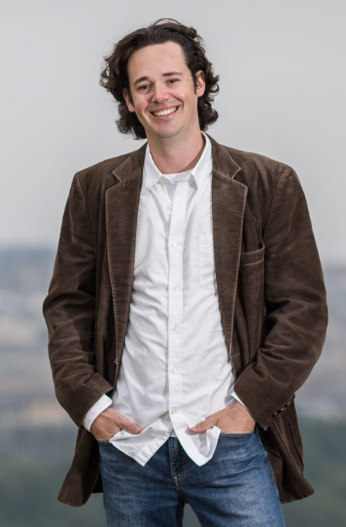 Michael Parsons standing and smiling with hands in jeans pockets