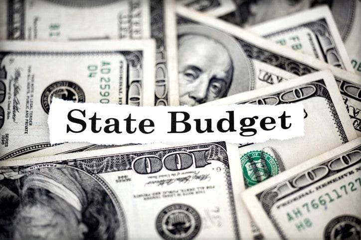 words state budget over pile of hundred dollar bills