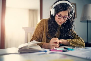 Teenage girl doing homework wearing headphones