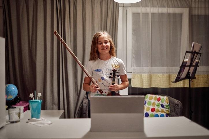 girl playing violin on online class during coronavirus quarantine