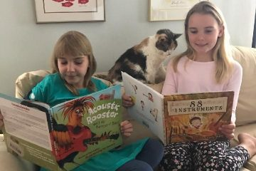 children reading books with cat on couch