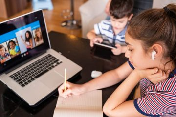 Teenage girl studying with video online lesson at home family in isolation Homeschooling and elearning