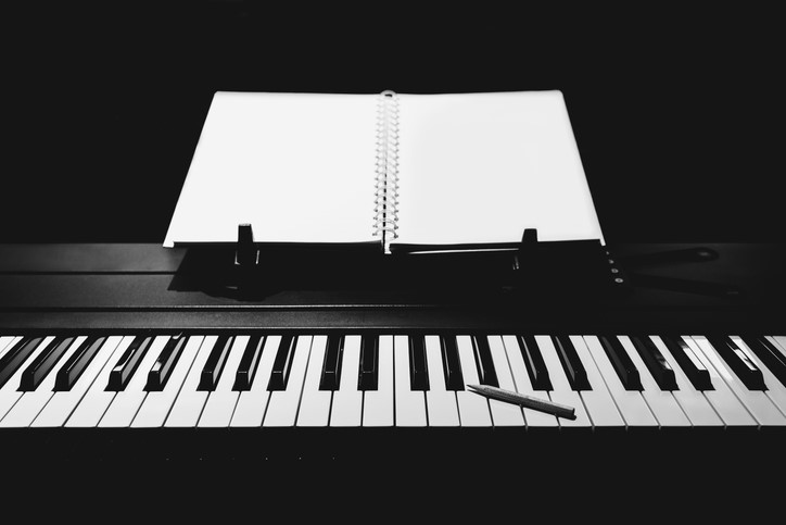 piano keyboard with notebook and pencil