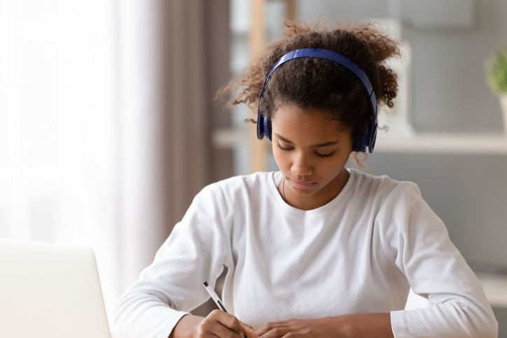 student writing and wearing headphones